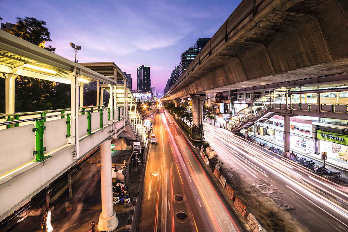 Traffic captured with blurred motion along Sukhumvit, the main road in Bangkok business district during sunset in thailand capital city