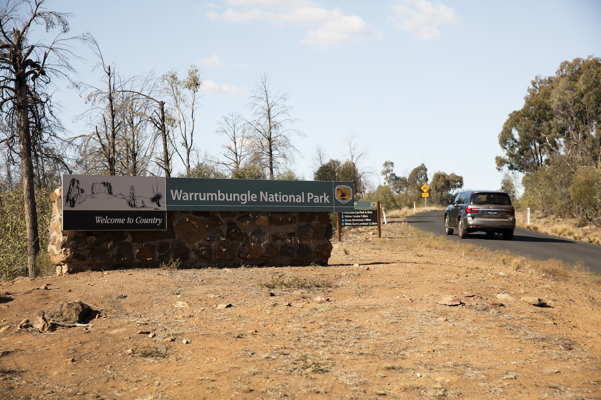 Warrumbungle: car driving past national park sign