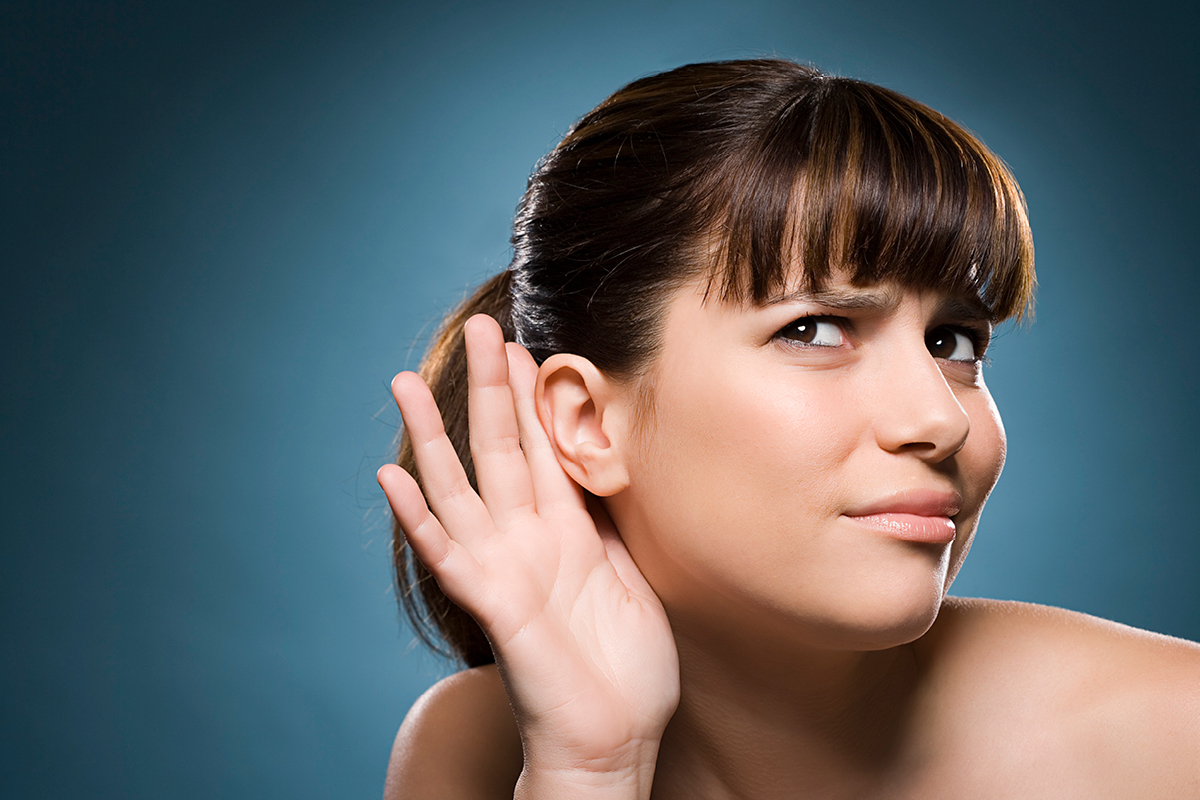 Woman with hand behind hear so she can listen better